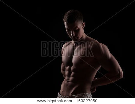 young athlete bodybuilder man isolated over black background