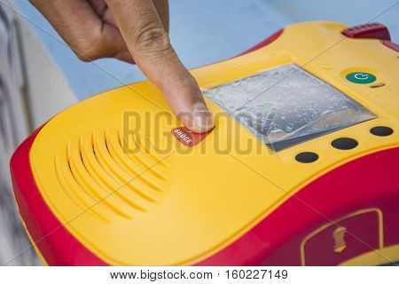 Automated External Defibrillator show finger push button shock