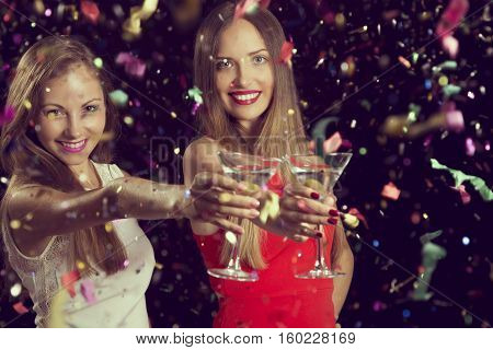 Two beautiful young women having fun at a party holding martini glasses and making a toast.
