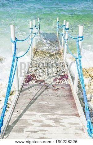 Half concrete and woooden pier with blue ropes leading into the sea. Adriatic coast Italy. Vertical composition