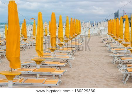 Rows of closed orange umbrellas and deckchairs on the empty beach before the storm. The beginning or back-end of the season concept.