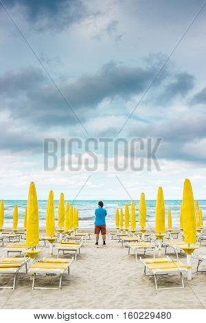 Lonely man is standing on the empty beach among the rows of closed umbrellas and deckchairs. The beginning or back-end of the season concept.