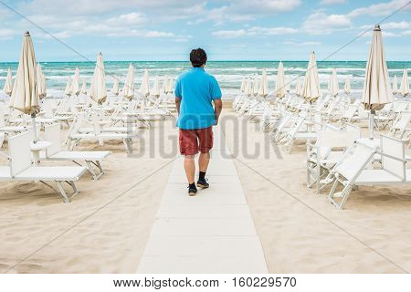 Lonely man walking on the empty beach among the rows of closed umbrellas and deckchairs. The beginning or back-end of the season concept.