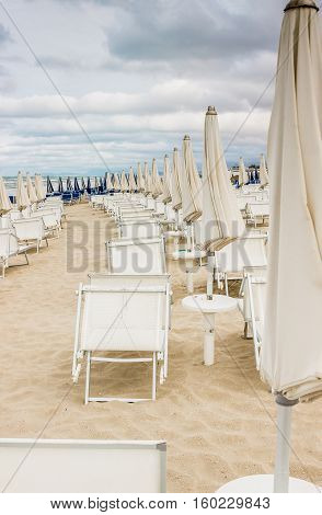Rows of closed white umbrellas and deckchairs on the empty beach before the storm. The beginning or back-end of the season concept.