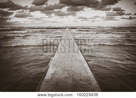 Perspective view of a concrete pier at the sea at sunset with dramatic sky and rolling waves. Stormy weather forces of nature concept
