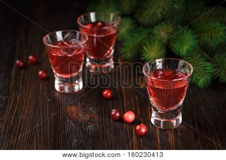 Three glasses of refreshing alcoholic cranberry cocktail with berries cranberries and spruce branches in the background on a wooden background.