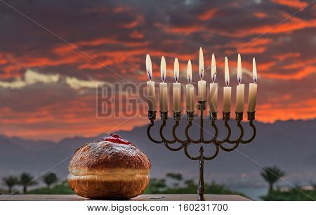 Jewish menorah with candles and sweet donuts are traditional symbols for Hanukkah holiday. Selective focus