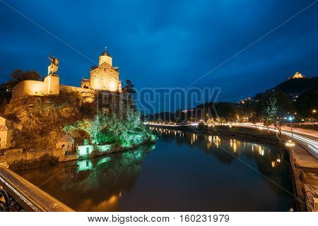 Night Evening Illuminated View Of The Metekhi Church And The Equestrian Statue Of King Vakhtang Gorgasali On The Metekhi Cliff In Old Historic District Of Tbilisi Georgia. Blue Hour. Blue Evening Sky.