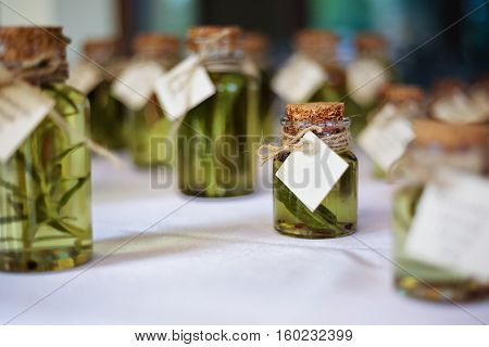 Miniature glass bottles of herb infused olive oil with labels, wedding gift, wedding favour