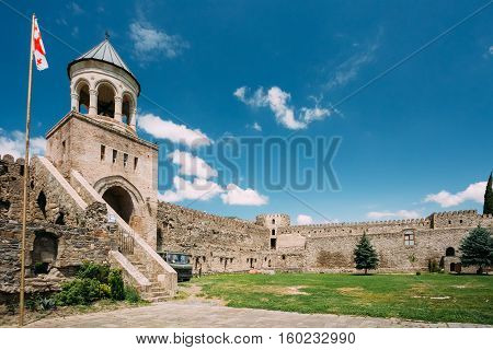 Mtskheta, Georgia. The View Of Inner Courtyard With A Tower Of Svetitskhoveli Cathedral Of The Living Pillar Surrounded By Gray Stone Fortified Wall Under Blue Cloudy Sky In Summer Spring Sunny Day.