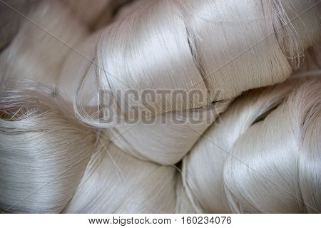 White silk fibres close-up. Illustration about silk production technology.