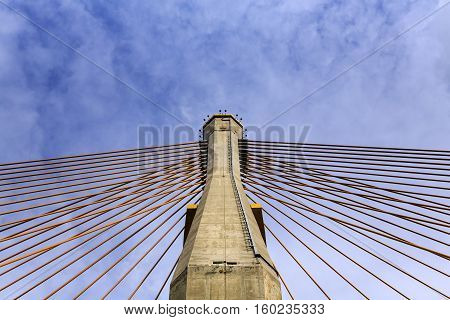 concrete tower and cable bridge with cloud and blue sky