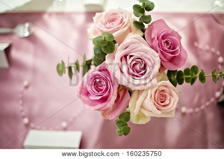 Bouquet of large pink roses placed on a pink table cloth in a restaurant. Romantic table setting.Flower centerpiece, wedding flower decoration