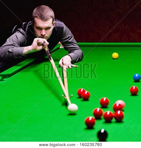Professional snooker player during snooker game, toned image, horizontal