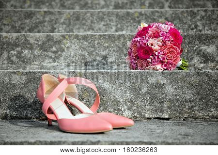 pink wedding shoes and wedding bouquet placed outdoor on a stairs bridal accessories close-up
