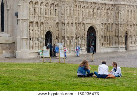 EXETER UK 11 July 2016: People sit on the lawn near the walls of the cathedral in Exeter. Devon. England