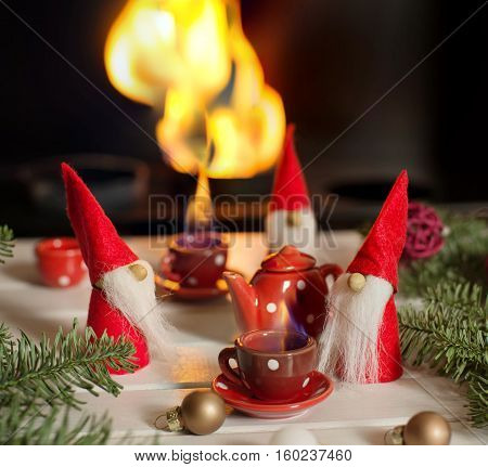 Santa's helpers sitting near fireplace with xmas decorations and drinking hot tea. Christmas fairy tail. Christmas still life.
