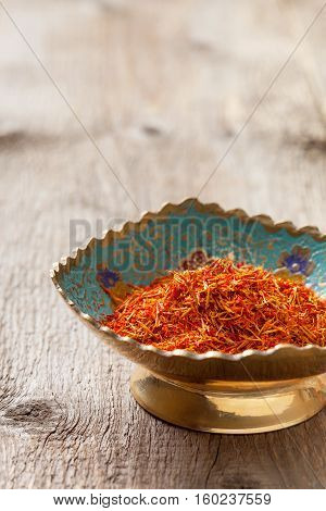 saffron in a metal bowl on the old wooden background