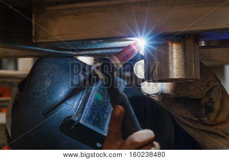 MIG-MAG welder overhead welding in steel structure manufacturing industry.