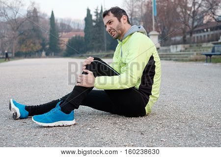 Runner with injured ankle while training in the city park in cold weather poster