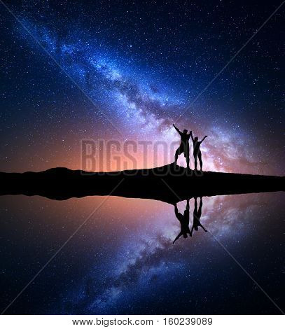 Milky Way. Night starry sky and silhouette of standing happy man and woman with raised up arms on the hill near the lake with sky reflection in water. Milky way with people on the mountain. Landscape