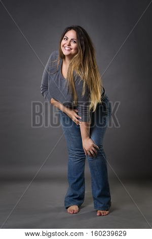 Young beautiful plus size model in blue jeans xxl woman on gray studio background full length portrait