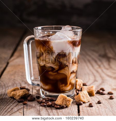 ice coffee in a tall glass with cream and coffee beans on a wooden background