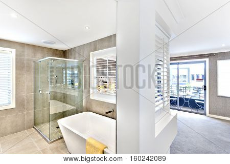 Modern washroom attached to the hallway to the outside windows or door which spreading sunlight the bathroom included a shower and washbasin