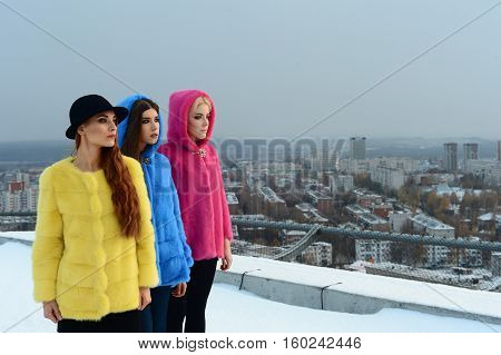 Three beautiful girls in colorful coats posing on the helipad.