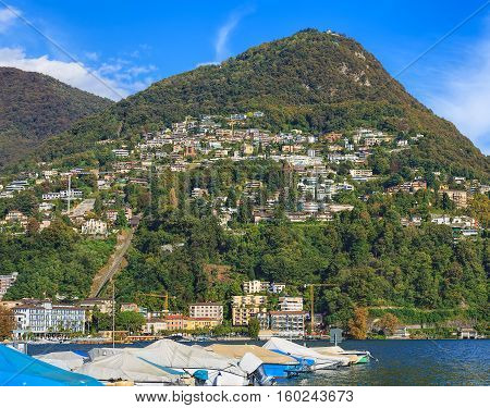 Lugano, Switzerland - 12 October, 2016: boats on Lake Lugano, mountain Monte Bre in the background. Lugano is the largest city of the Swiss Canton of Ticino.