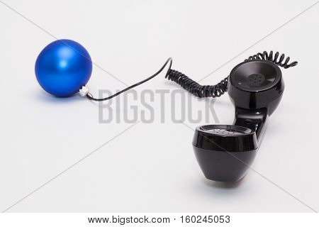 Old phone reciever and cord connection with Christmas decoration. Christmas hotline concept.