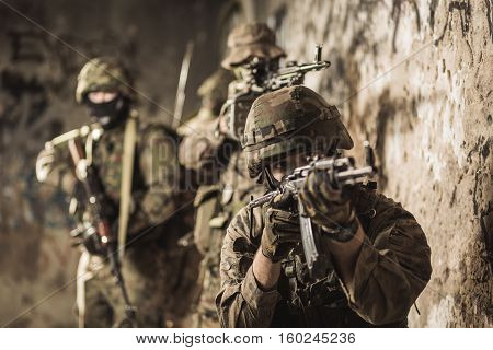 Portrait of young army soldier holding automatic weapon during war