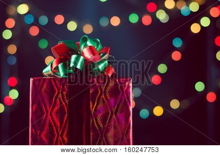 Red christmas gift box with ribbon and bow on bokeh lights background