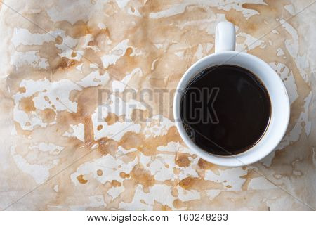 Cup of coffee on coffee stains background top view