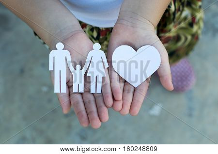 Children hands holding small model of heart and family concept family