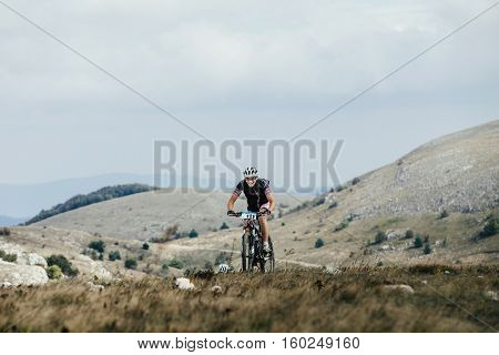 Privetnoye Russia - September 21 2016: young athlete cyclist mountainbiker going uphill on a sports bicycle during Crimean race mountainbike