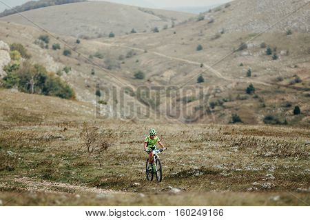 Privetnoye Russia - September 21 2016: young male cyclist mountainbiker riding on a mountain valley during Crimean race mountainbike