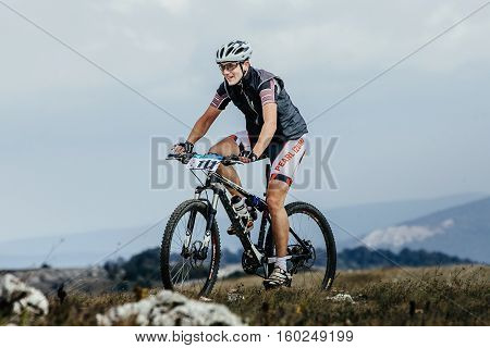 Privetnoye Russia - September 21 2016: young athlete cyclist mountainbiker against a mountain landscape during Crimean race mountainbike