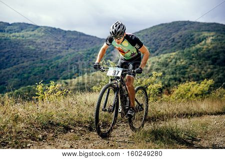 Privetnoye Russia - September 22 2016: male athlete mountainbiker rides mountain trail during Crimean race mountainbike