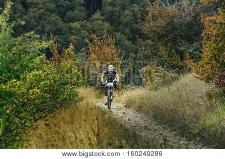 Privetnoye Russia - September 22 2016: male athlete mountainbiker rides uphill in mountain trail during Crimean race mountainbike