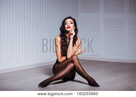Beautiful fashion portrait of young sexy brunette woman with perfect body, long legs, red lips, wearing seductive black lingerie and tights.