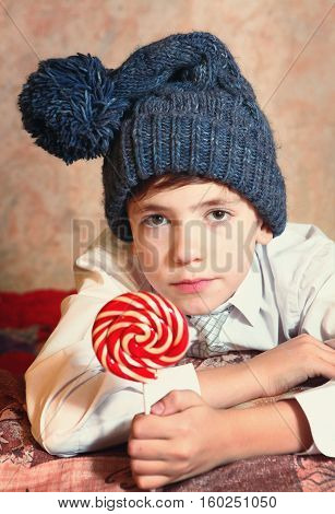 cute preteen boy in blue knitted hat with red and white round candy on stick