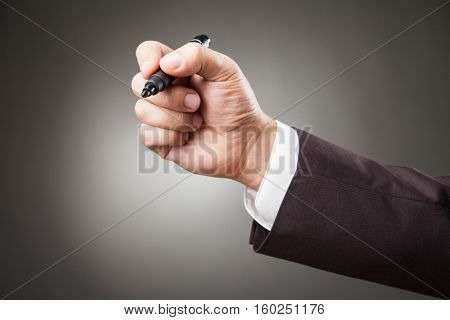 Hand of man wearing suit holding black marker. Horizontal studio shot