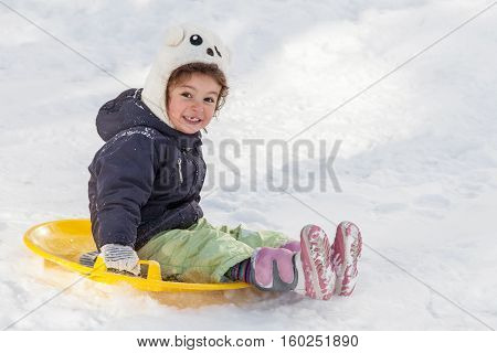 Cute little girl with saucer sleds outdoors on winter day ride down the hills winter games and fun