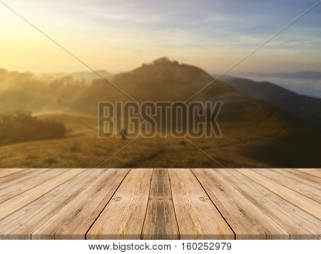 Wooden board empty table in front of blurred background. Perspective brown wood table over blur sunset mountain landscape background - can be used mock up for display or montage your products.