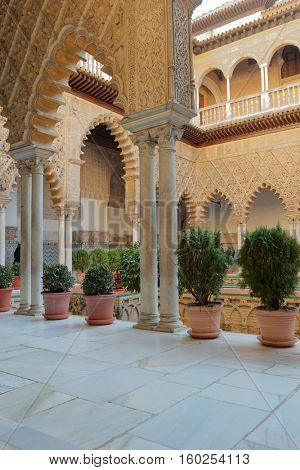 SEVILLE, SPAIN - JANUARY 3, 2013: Tourists in the Real Alcazar of Seville, a royal palace, originally a Moorish fort. Since 1987, it is listed as UNESCO World Heritage site