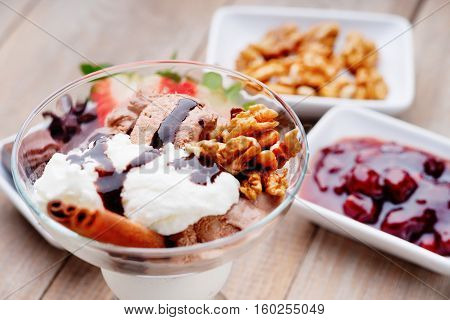 Ice cream sundae, walnuts and jam on a table