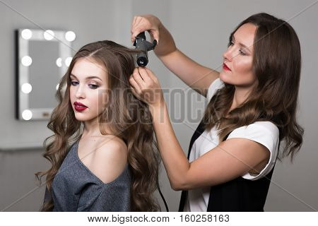 Hairdresser using curling tongs on client's hair at salon, process of hairstyle. Portret of two beautiful women