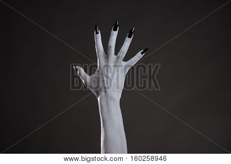 Spooky white hand with black nails, studio shot on black background