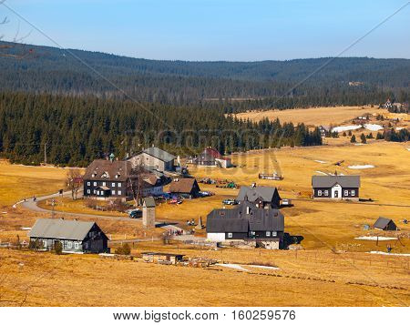 Mountain village Jizerka in Jizera Mountains in Northern Bohemia, Czech Republic. Simple huts around mountain brook on sunny spring day with yellow grass and rest of snow fields.